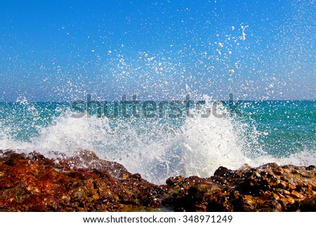 Big waves breaking on the shore with sea foam. Royalty-Free Stock Photo #348971249
