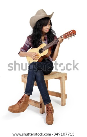 Cowgirl playing ukulele on a wooden chair, isolated on white background
