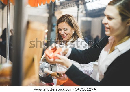 MILAN, ITALY - NOVEMBER 7: People visiting Eat Market, a street food parade with international dishes  in Milan on November, 7 2015. Saleswomen preparing and serving cannoli to customers, smiling #349181294