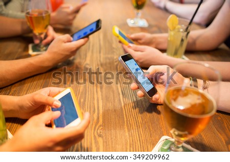 leisure, technology, lifestyle and people concept - close up of hands with smartphones messaging at restaurant Royalty-Free Stock Photo #349209962