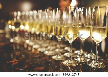 A lot of wine glasses with a cool delicious champagne or white wine at the bar. Alcohol background. #349213745