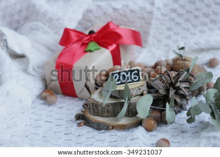 Christmas box. Christmas craft box with a red ribbon. Christmas hazelnuts. Christmas Eucalyptus. green felt New Year tree. Christmas kniited background  #349231037