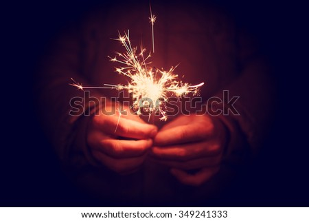 Man holding bright festive Christmas sparkler in hand, tinted photo #349241333