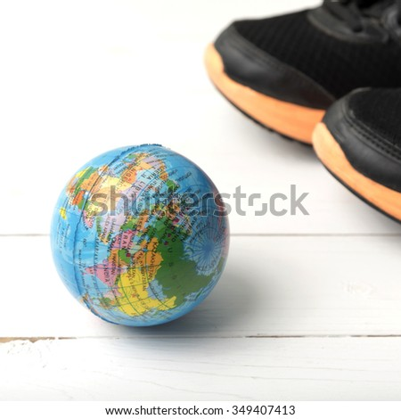 running shoes and earth ball on white wood table concept world healthy #349407413