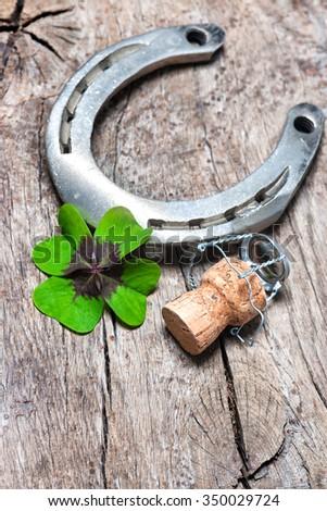 Horseshoe, shamrock and champagne cork on old wooden #350029724