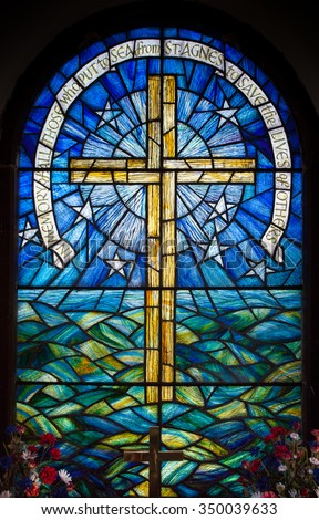 Stained glass window in a church on St Agnes, Isles of Scilly, U.K. Depicting a cross against the sky and sea. #350039633