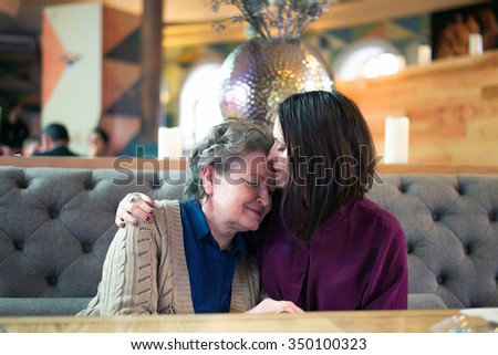 young woman kisses her senior mother