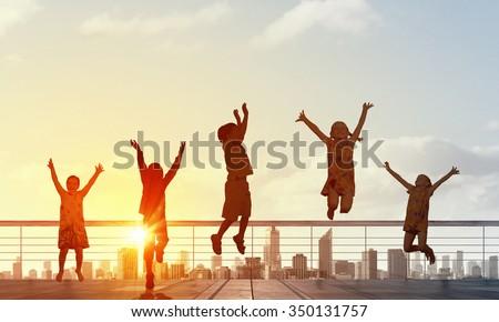 Silhouettes of group of children jumping high joyfully on sunrise background #350131757