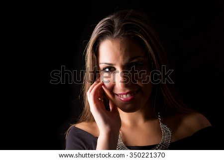 Young beautiful woman standing against black background #350221370