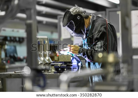 Industrial worker with protective mask welding inox elements in steel structures manufacture workshop. Royalty-Free Stock Photo #350282870