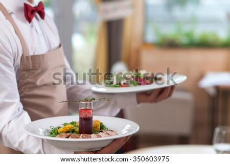 Close up of hands of young waiter holding two plates of delicious food Royalty-Free Stock Photo #350603975