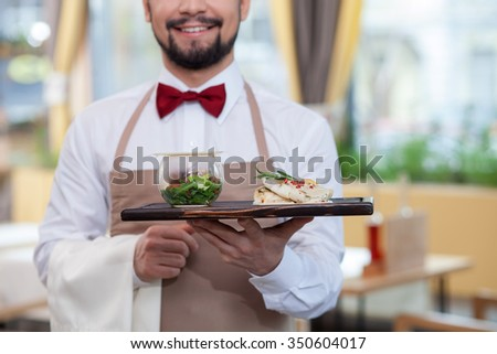 Close up of cute young waiter holding a tray of food. He is standing and smiling in the restaurant  Royalty-Free Stock Photo #350604017