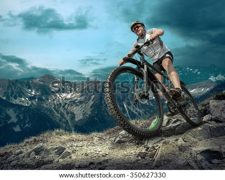 Man in helmet and glasses stay on the bicycle under sky with clouds. #350627330