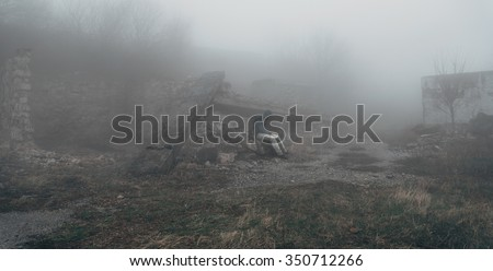 Man in a hood sitting among ruins at mystical mist, post-apocalyptic scene Royalty-Free Stock Photo #350712266