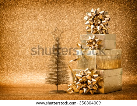 Golden christmas tree decoration with gift boxes. Holidays background. Vintage style toned picture