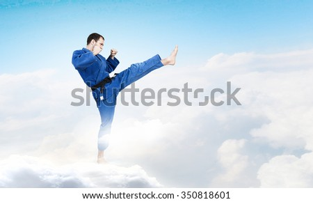 Young determined karate man on cloud high in sky #350818601