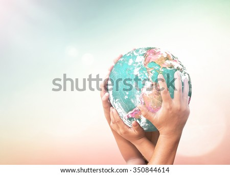 International human solidarity day concept: Children hands holding earth globe over blurred abstract nature background. Elements of this image furnished by NASA Royalty-Free Stock Photo #350844614