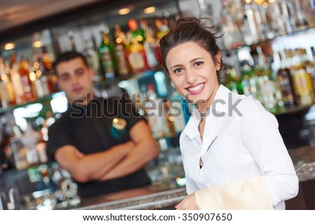 waitress restaurant catering service. Female cheerful restaurant worker with barman at background Royalty-Free Stock Photo #350907650