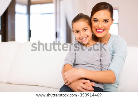 attractive young woman sitting on couch with her daughter #350914469