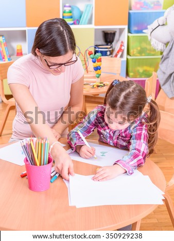 kindergarten teacher helping cute girl to draw and paint #350929238