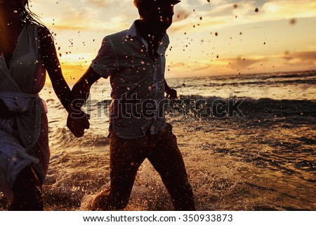 beautiful sunset in the ocean and happy couple running together #350933873