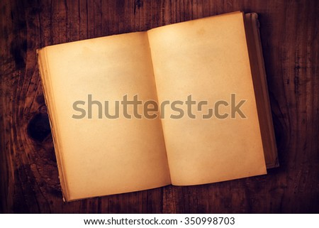 Top view of old open book with blank pages on wooden desk as copy space, retro toned image.