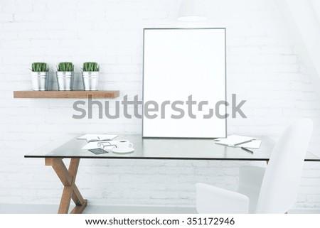 Blank white picture frame on glassy table in modern loft room, mock  up