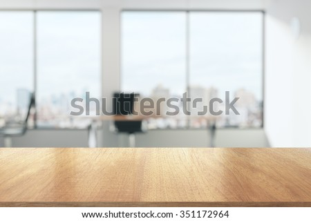 Wooden table in sunny office with big windows Royalty-Free Stock Photo #351172964