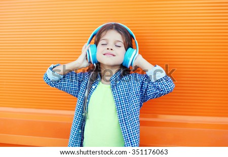 Happy smiling child enjoys listens to music in headphones over colorful orange background #351176063