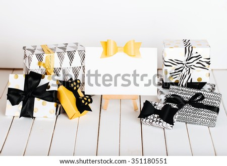 Easel with sheet of paper and modern painted paper black and white presents wrap #351180551