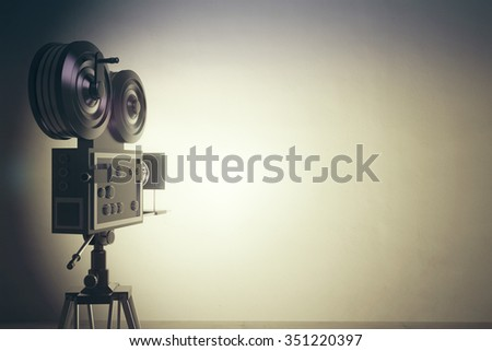Old style movie camera with white wall, vintage photo effect #351220397