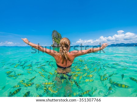 Woman swimming with snorkel surrounded by fish, Andaman Sea, Thailand #351307766