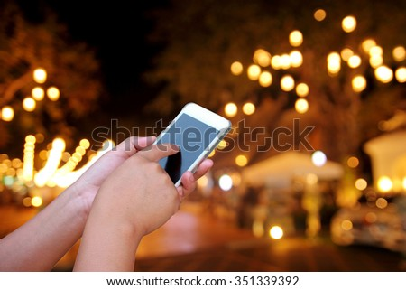 hand hold and touch screen smart phone, on abstract  blurred photo night festival on street #351339392