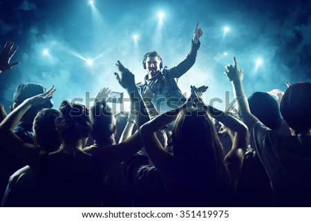 Dj in front of crowd Royalty-Free Stock Photo #351419975