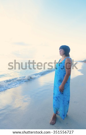 a lonely middle-aged woman brunette looks into the distance the ocean on the sunrise #351556727