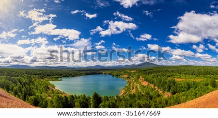 Panorama of the lake among hills with cloudy blue sky #351647669