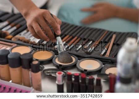 Make-up artist using natural animal hair brush to apply pressed powder Royalty-Free Stock Photo #351742859