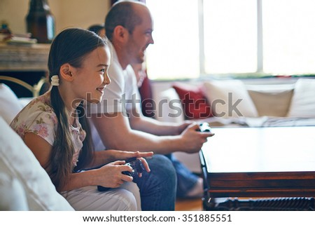Smiling girl playing video games with her father #351885551