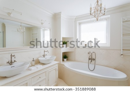 Horizontal picture of a showy bathroom designed in creamy colors