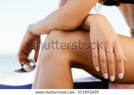 Woman in a swimsuit sits on the coast, in her hand sunglasses. Close-up. Warm colors. #351893609