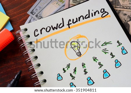 Notebook with crowd funding  sign on a table. Business concept.