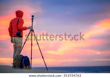 Photographer in red jacket with hood filming with small action camera on the tripod beautiful sunrise on the sand dunes in the early morning. Time lapse filming process #351934763