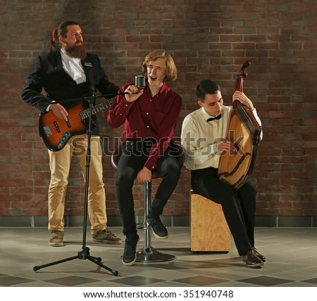 Man's musical band on brick wall background in the studio #351940748