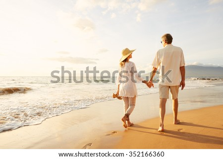 Happy Romantic Middle Aged Couple Enjoying Beautiful Sunset Walk on the Beach. Travel Vacation Retirement Lifestyle Concept #352166360