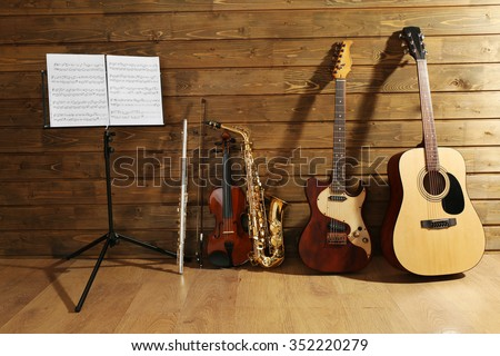 Note holder against musical instruments on wooden background Royalty-Free Stock Photo #352220279