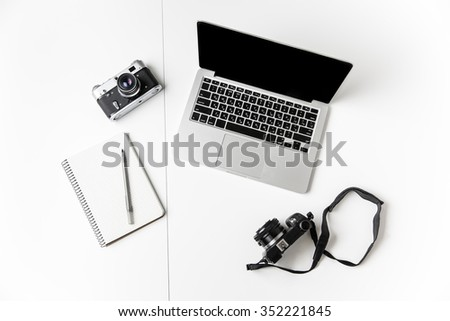 Top view of two cameras, notepad with pen and blank screen laptop isolated over white background #352221845