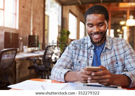 Designer Sitting At Meeting Table Texting On Mobile Phone #352279322