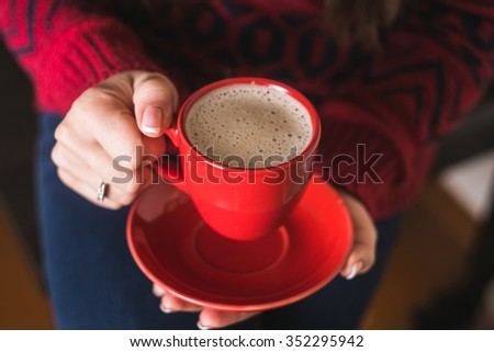 The girl in the red sweater holding a red cup of coffee. Beautiful gel lacquer. French manicure with silver diamonds. Women's hands. #352295942