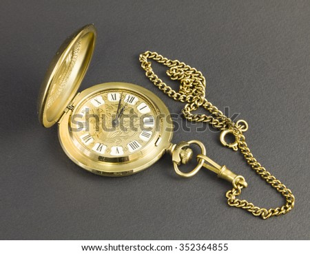 Watches made of yellow metal with black Roman numerals on a dark background. #352364855