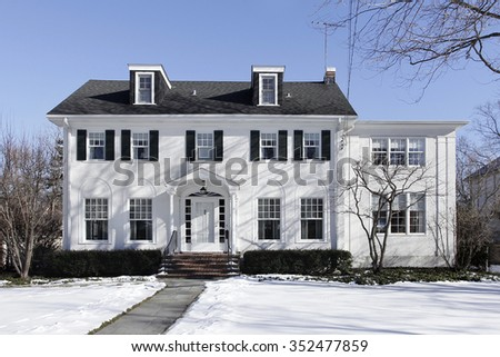 Suburban home in winter with black shutters #352477859